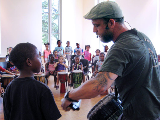 Boy assisting presenter at drum circle program