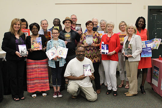 Sixteen local authors holding their books