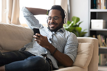 Man relaxing on couch with headphones